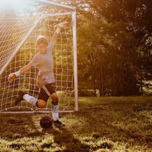 custom soccer uniforms kid kicking ball in goal